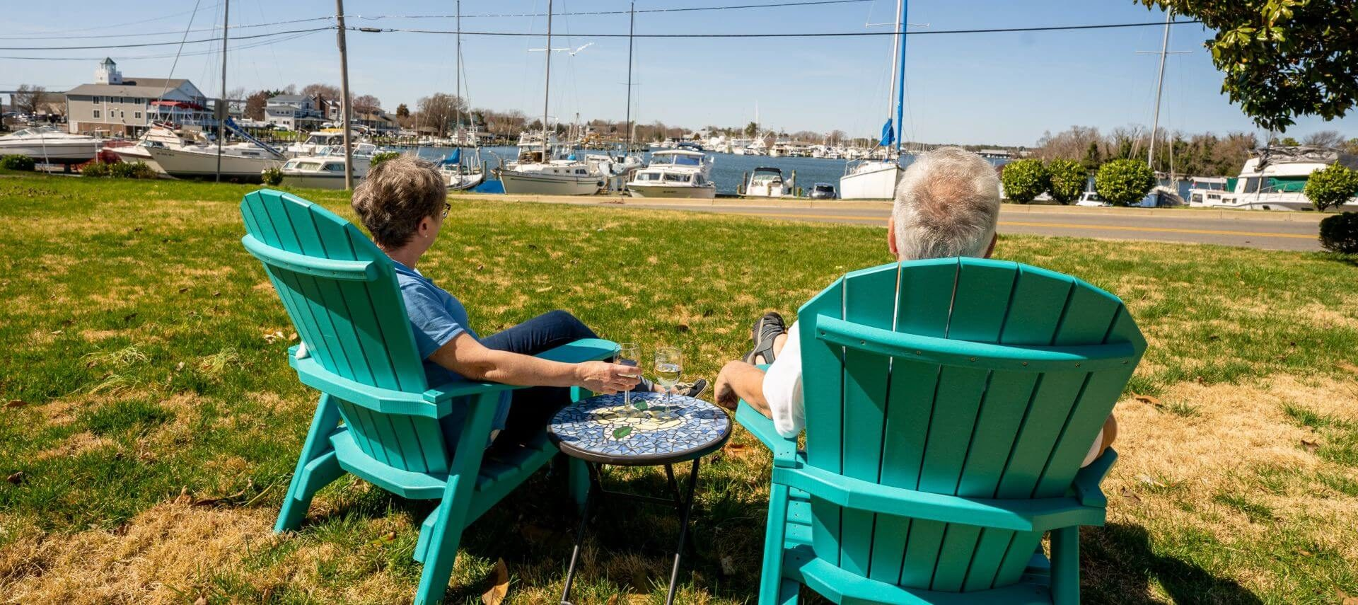 man and woman sitting in chairs looking at harbor