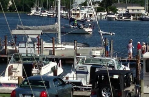Marina with boats tied up at the dock and one sailing away