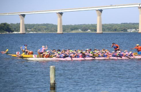 Two long boats filled with many people rowing and racing in the water
