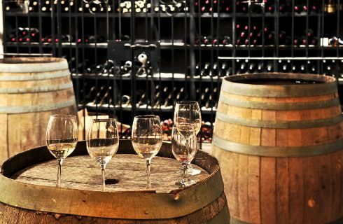 Wine glasses on top of a wooden barrel surrounded by wine storage