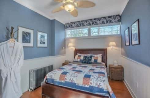 Bedroom with blue-gray walls, white wainscoting, hardwood flooring, dark wooden bed, and ceiling fan