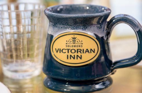 Close up view of blue stoneware mug with Solomons Victorian Inn logo in yellow