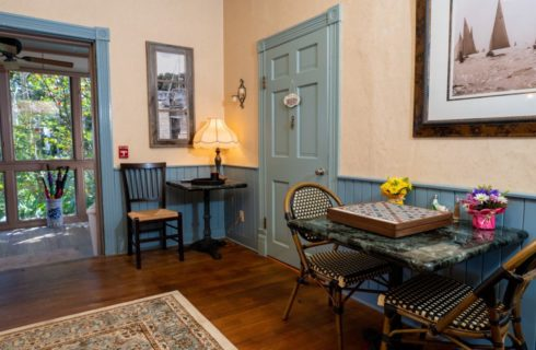 Large room with cream walls and blue-gray wainscoting, hardwood floors, area rug, and table for two with wooden chess board