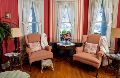 Sitting area with red walls, white trim, hardwood flooring, two peach arm chairs, and three large windows