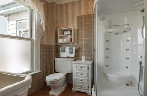 Bathroom with taupe tile, hardwood flooring, steam-massage shower, white pedestial sink, and white toilet
