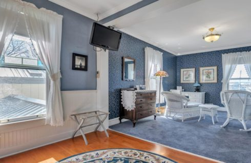 Bedroom with blue-gray walls, white wainscoting, hardwood flooring, and sitting area with white wicker furniture