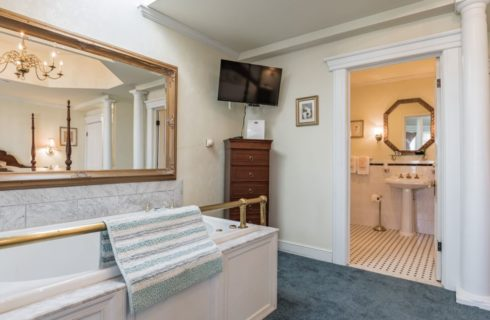 Bedroom with light cream walls, white trim, blue carpeting, white whirlpool tub, TV mounted on the wall, and view into bathroom
