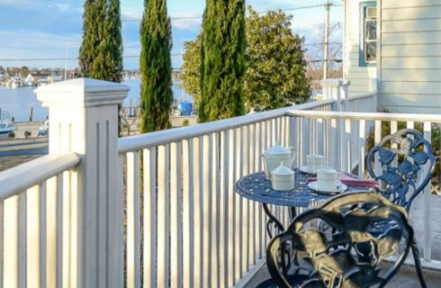 Patio with a white railing, rod-iron table and chairs, and view of the marina