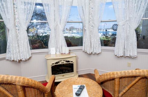 Two wicker arm chairs with a small wicker table near a fireplace next to large windows with a view of the marina