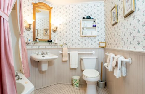 Bathroom with floral wallpaper, white wainscoting, tile flooring, white sink, white toilet, and wooden mirror