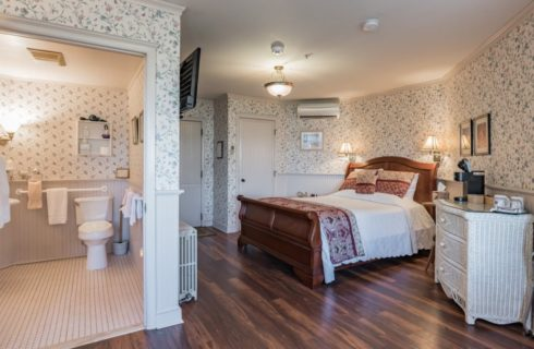 Bedroom with floral wallpaper, white wainscoting, hardwood flooring, wooden sleigh bed with white and red bedding, white wicker dresser, and view into bathroom
