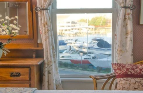 Close up view of wooden dresser, wicker chair, and window with a view of the marina