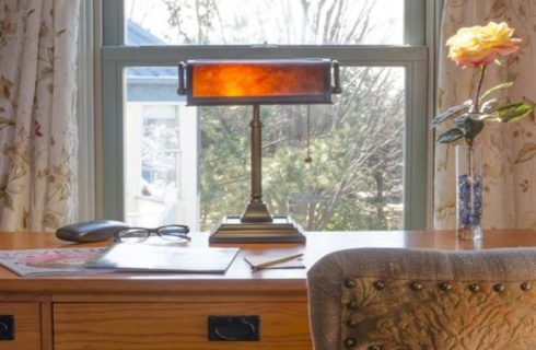 Close up view of wooden desk with lamp, magazines, glasses, and yellow rose in a glass vase and a window with view to the outside