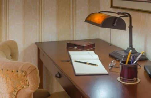 Wooden desk with open journal, green pen, lamp, glasses, cup with pens, and upholstered chair