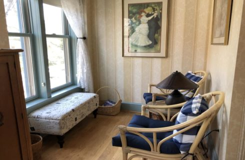 Sitting area with light tan striped wallpaper, blue-gray trim, hardwood flooring, bench seat near window, and two wicker chairs with navy pillows
