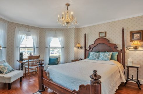 Bedroom with light cream wallpaper, white trim, hardwood flooring, wooden furniture, cream bedspread, and a table and chair near three large windows