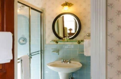 Bathroom with light cream wallpaper, teal tiles, tiled stand up shower, white pedestal sink, and round wooden mirror