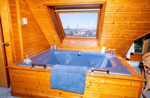 Room with floor to ceiling wood paneling, blue jetted tub surrounded by wood paneling, and large window with views to the outside