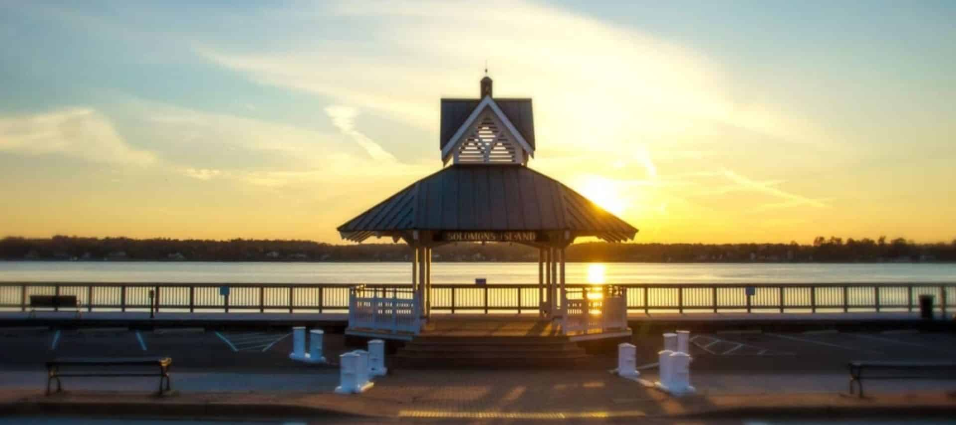 Wooden gazebo next to a body of water with land and the sunset in the background