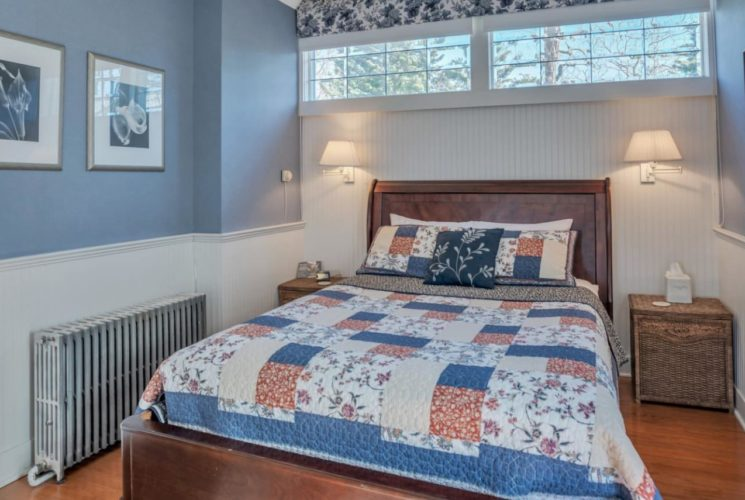 Bedroom with blue-gray walls, white wainscoting, hardwood flooring, dark wooden bed, and rack with hanging white robes