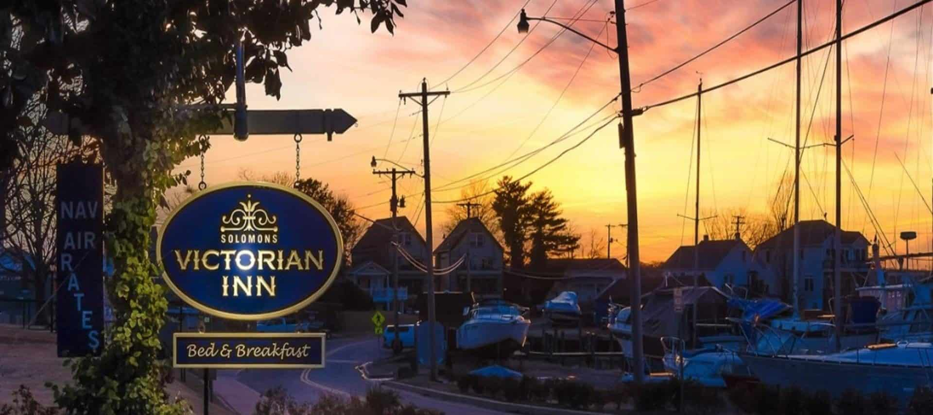 View of the Solomons Victorian Inn sign with the marina and buildings in the background at sunset