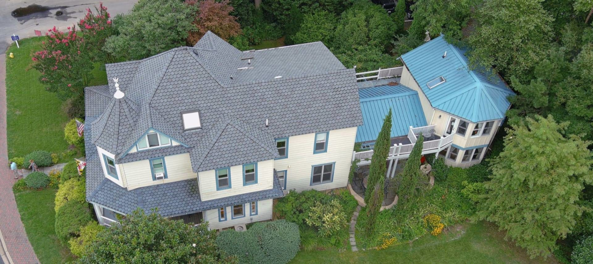 Aerial view of the property surrounded by lush greenery, bushes, and trees