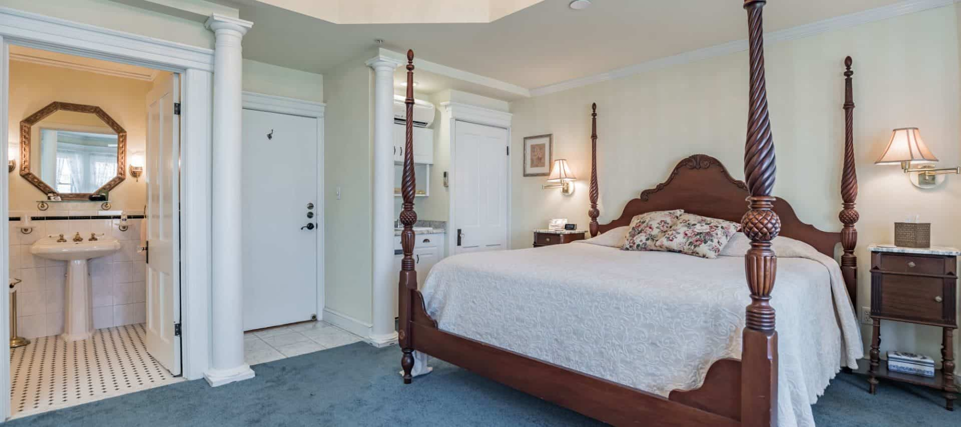 Bedroom with light cream walls, white trim, blue carpeting, four-poster wooden bed, white bedding, and view into bathroom