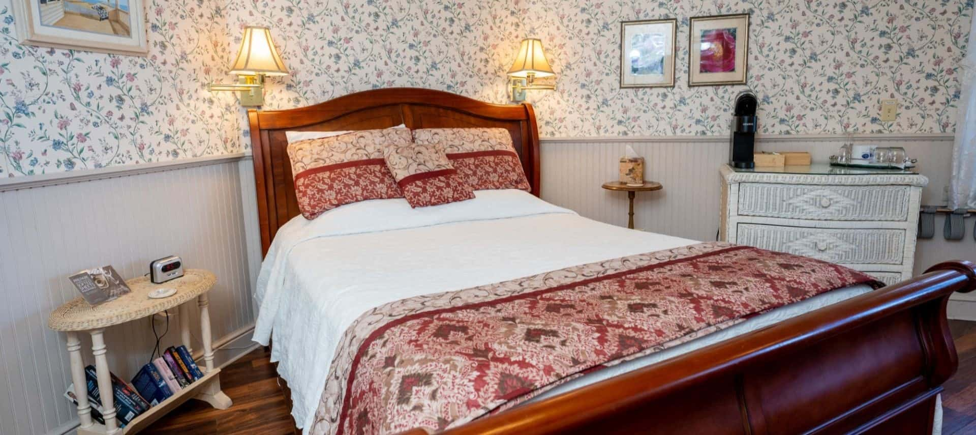 Bedroom with floral wallpaper, white wainscoting, hardwood flooring, wooden sleigh bed with white and red bedding, and white wicker dresser