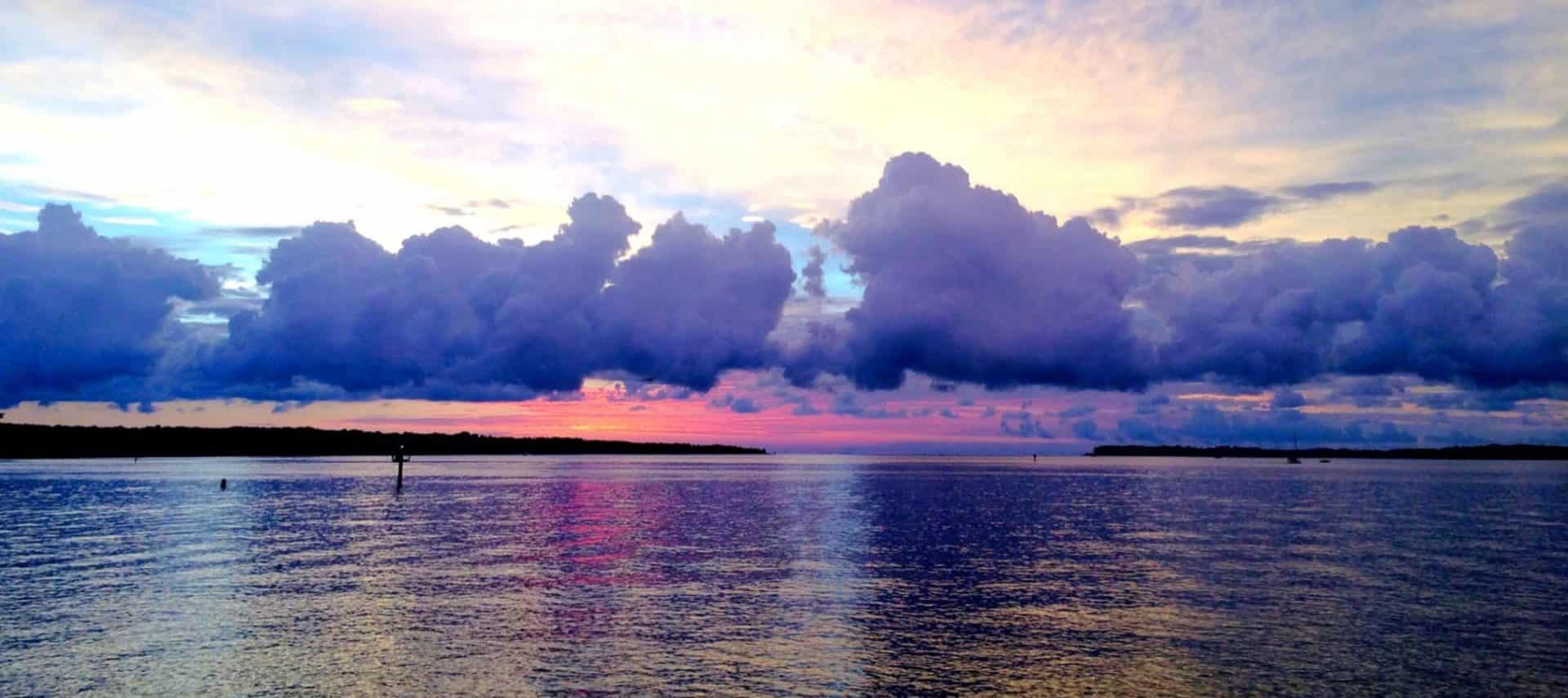 View of the bay with land in the background at sunset with blue, purple and pink clouds in the sky