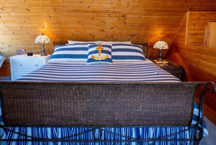 Room with floor to ceiling wood paneling, blue carpeting, dark brown wicker sleigh bed with blue and white striped bedding, and white wicker dresser